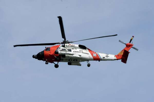 A Coast Guard helicopter searches for a man who was swept off of a sandbar into the water while walking out to Charles Island at Silver Sands State Park in Milford on 7/21/2017. Arnold Gold / Hearst Connecticut Media