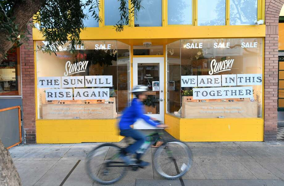 A boy rides his bike passed a supportive sign posted on a storefront in San Francisco on April, 1, 2020, during the novel coronavirus outbreak. Photo: JOSH EDELSON/AFP Via Getty Images / AFP or licensors