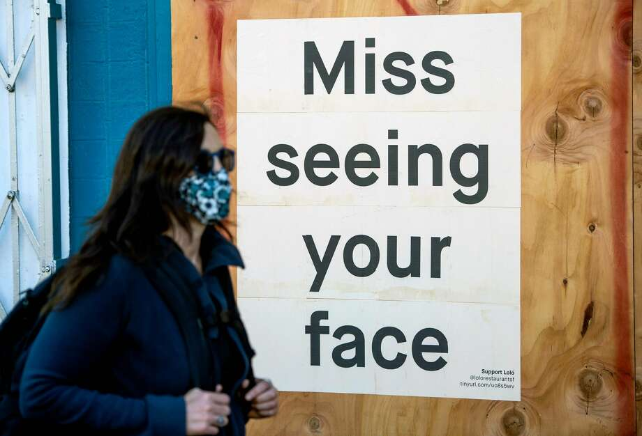 A woman in a face mask walks by a sign posted on a boarded up restaurant in San Francisco on April, 1, 2020, during the novel coronavirus outbreak. Photo: JOSH EDELSON/AFP Via Getty Images / AFP or licensors