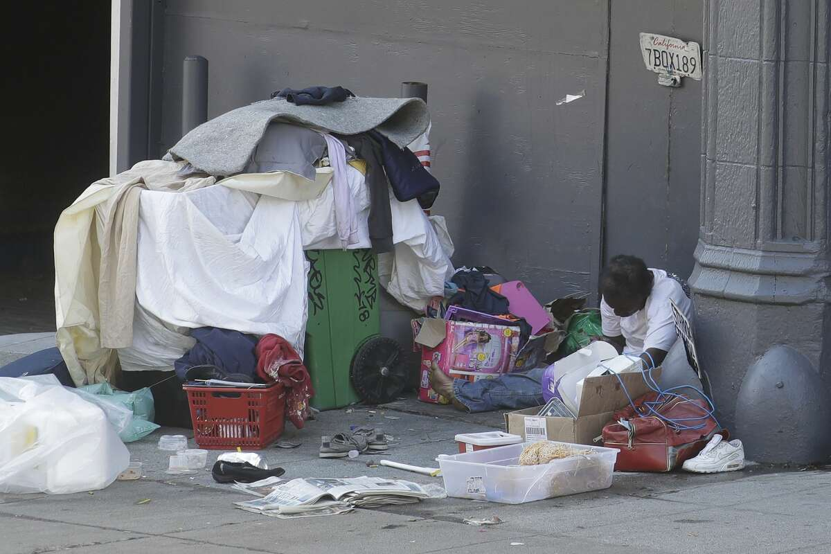 A homeless person sits on the street in San Francisco, Thursday, April 2, 2020. Since the beginning of an international pandemic, officials in California have said one population is particularly vulnerable to contracting the coronavirus and spreading it to others: the homeless.