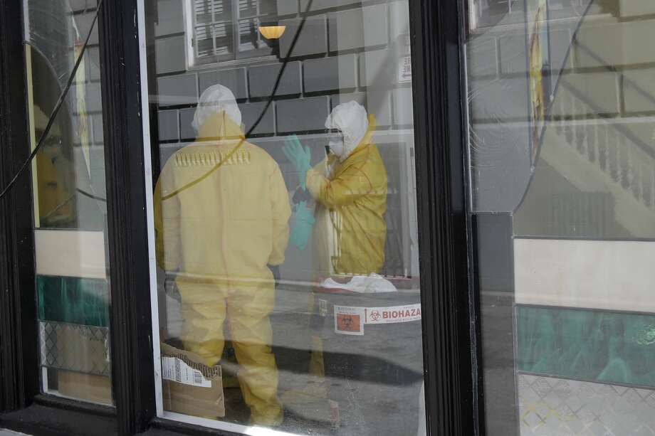 Men in hazardous material suits work inside the Abigail Hotel in San Francisco, Thursday, April 2, 2020. The hotel is one of several private hotels San Francisco has contracted with to take vulnerable people who show symptoms or are awaiting test results for the coronavirus. Photo: Jeff Chiu/Associated Press / Copyright 2020 The Associated Press. All rights reserved