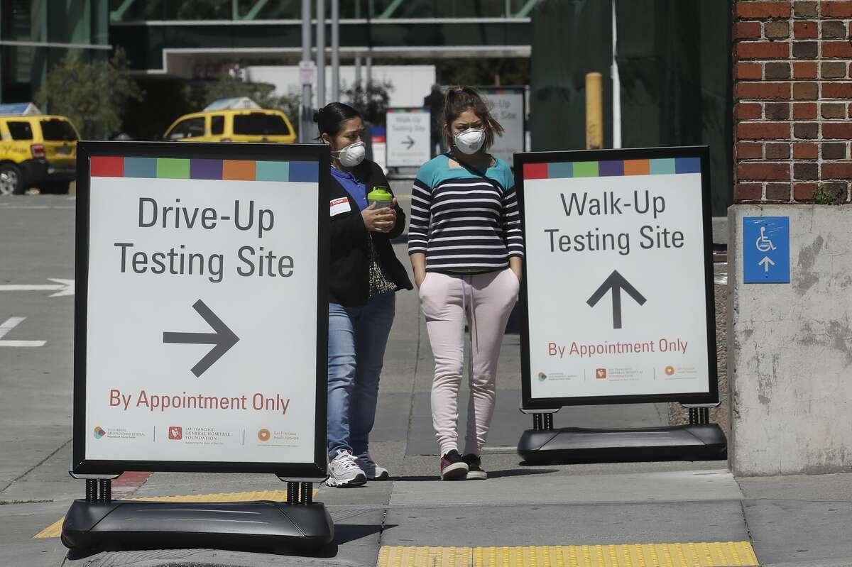 Women wear masks while walking between signs advising COVID-19 drive up and walk up testing sites at Zuckerberg San Francisco General hospital in San Francisco, Thursday, April 2, 2020.