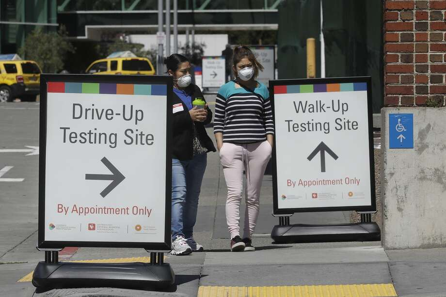 Women wear masks while walking between signs advising COVID-19 drive up and walk up testing sites at Zuckerberg San Francisco General hospital in San Francisco, Thursday, April 2, 2020. Photo: Jeff Chiu/Associated Press / Copyright 2020 The Associated Press. All rights reserved