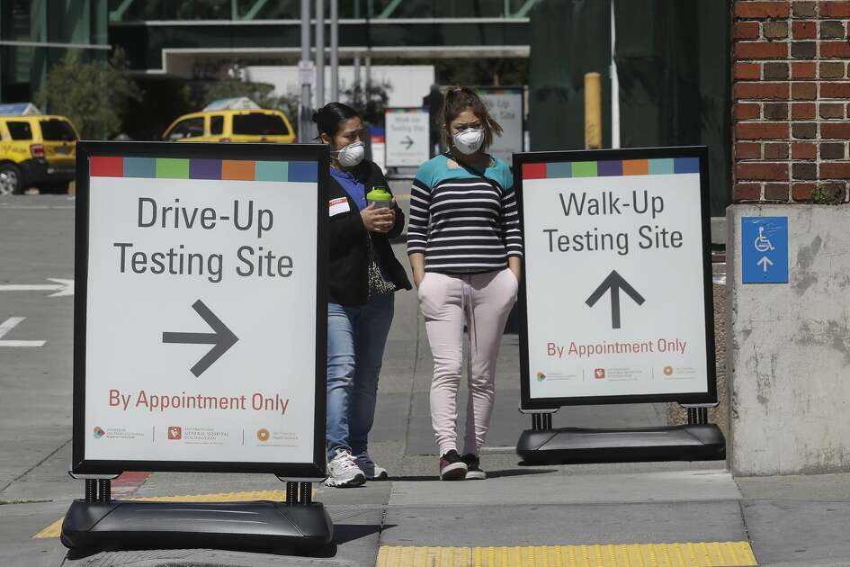 Women wear masks while walking between signs advising COVID-19 drive up and walk up testing sites at Zuckerberg San Francisco General hospital in San Francisco, Thursday, April 2, 2020.
