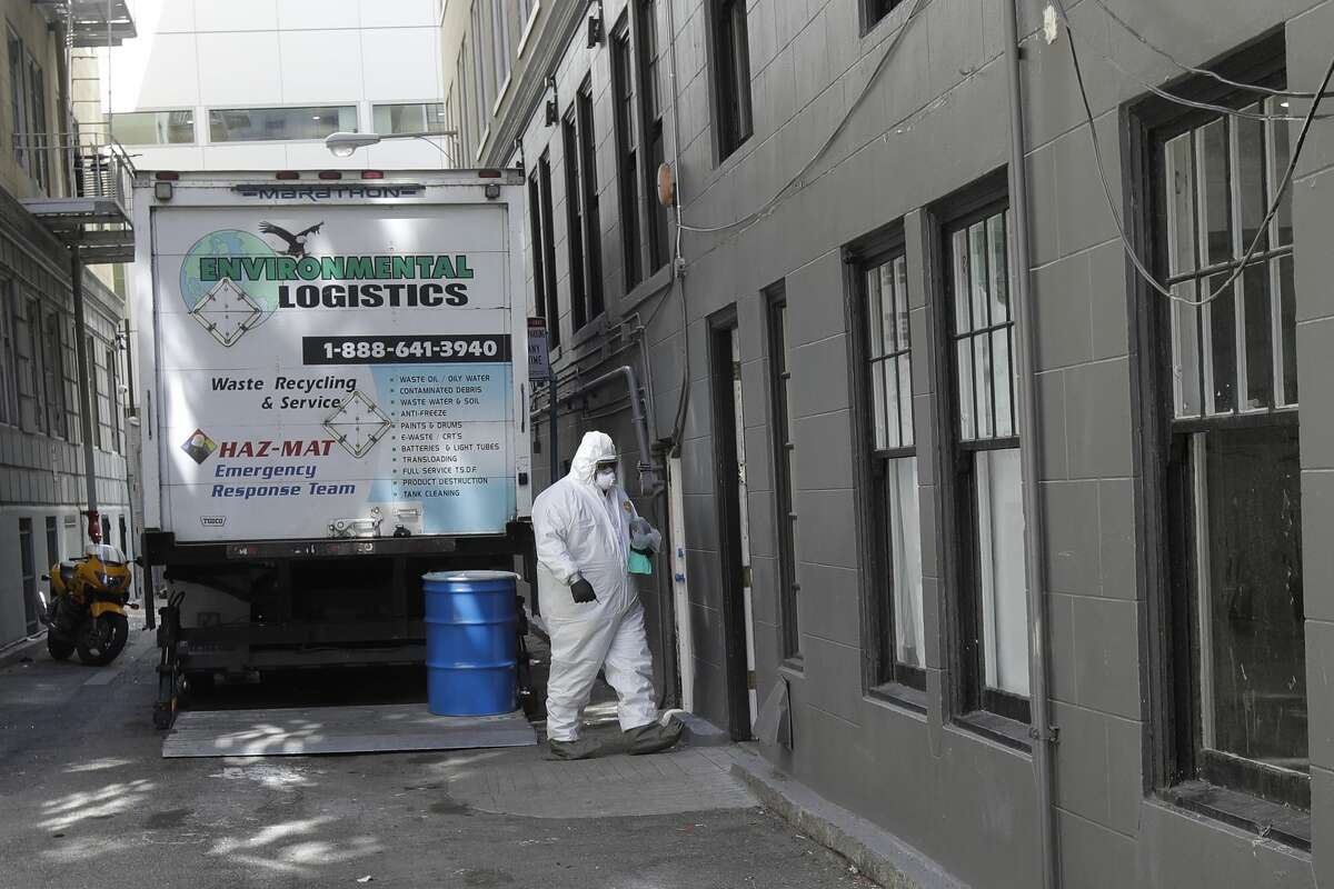 A worker in a haz-mat suit walks to an entrance to the Abigail Hotel in San Francisco, Thursday, April 2, 2020. Since the beginning of an international pandemic, officials in California have said one population is particularly vulnerable to contracting the coronavirus and spreading it to others: the homeless. The Abigail Hotel is one of several private hotels San Francisco has contracted with to take vulnerable people who show symptoms or are awaiting test results for coronavirus.