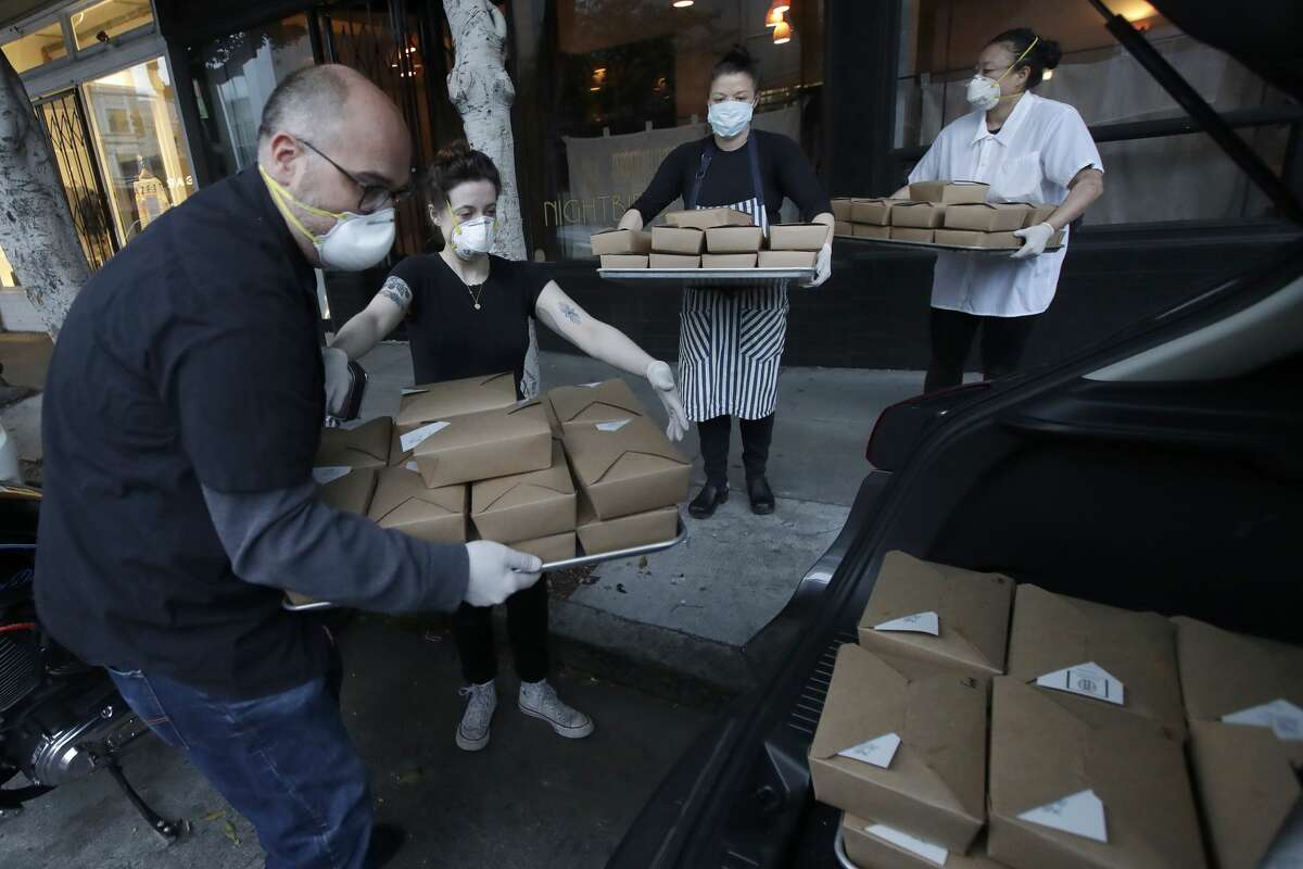 In this Friday, March 27, 2020, photo, Nightbird Restaurant general manager Ron Boyd, from left, pastry chef Hope Waggoner, chef and owner Kim Alter and sous chef Bailey Walton pack dinner boxes into Alter's car that were delivered to hospital workers in San Francisco. A group of tech-savvy, entrepreneurial San Francisco friends wanted to help two groups devastated by the coronavirus pandemic. They came up with a plan that involved soliciting donations, tapping friends in the restaurant world and getting San Francisco hospitals to accept free food cooked up by some of the city's top chefs.