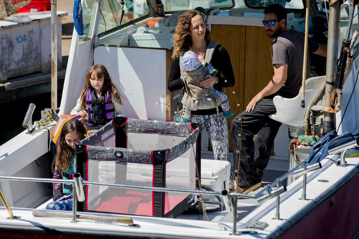"""Adam Sewall steers his fishing boat and his wife Eleza Jaeger carries their 9-month-old Shel Jaeger while their daughters Hazel Jaeger (left), 9, and Rhye Jaeger, 6, sport life jackets as they set off from the Berkeley Marina in Berkeley, Calif. Wednesday, April 1, 2020. Before the shelter-in-place orders, the family operated a fishing charter boat, but that business has come to a halt. They've developed a big social media presence around """"Fish School,"""" their homeschooling from the boat, and are now catching fish while other commercial fishing boats have stopped."""