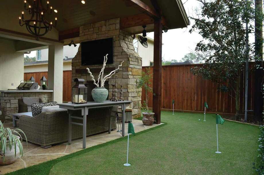 This outdoor living/kitchen space and putting green guarantee fun for all.