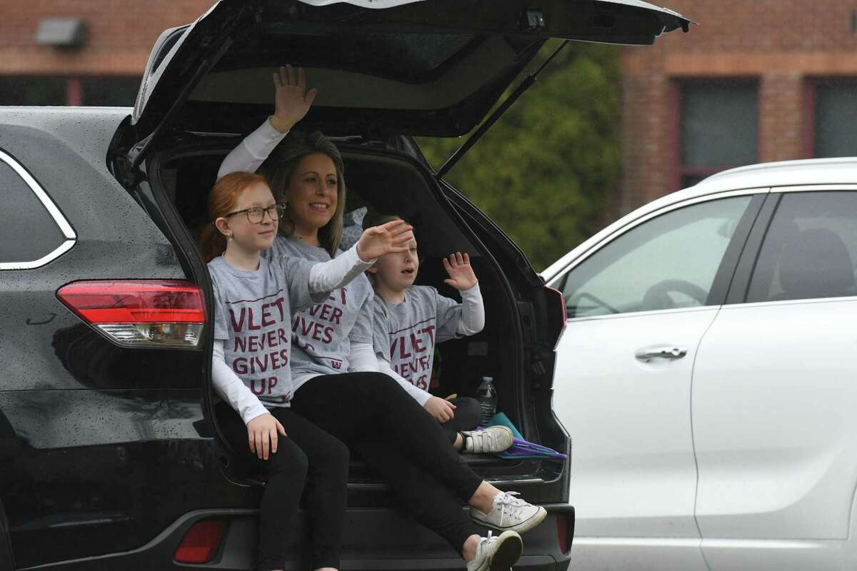Abigail Gray, 9, left, her mom, Erica, center, and sister, Alivia, 6, right, cheer for their Watervliet Elementary School teachers and staff during a caravan parade through the city on Friday, April 3, 2020, in Watervliet, N.Y. Students and family members came to their doorsteps to reconnect with school staff members following the coronavirus lockdown. (Will Waldron/Times Union)
