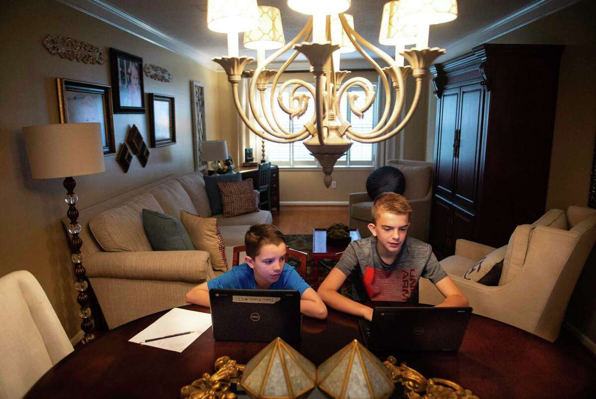 Brothers John Evan, 9, left, an elementary student, and Mason Sinclair, 12, a middle school student, extend their learning with virtual projects on their Chromebooks at their home on Friday, March 20, 2020, in Decatur, Ala. (Dan Busey/The Decatur Daily via AP)