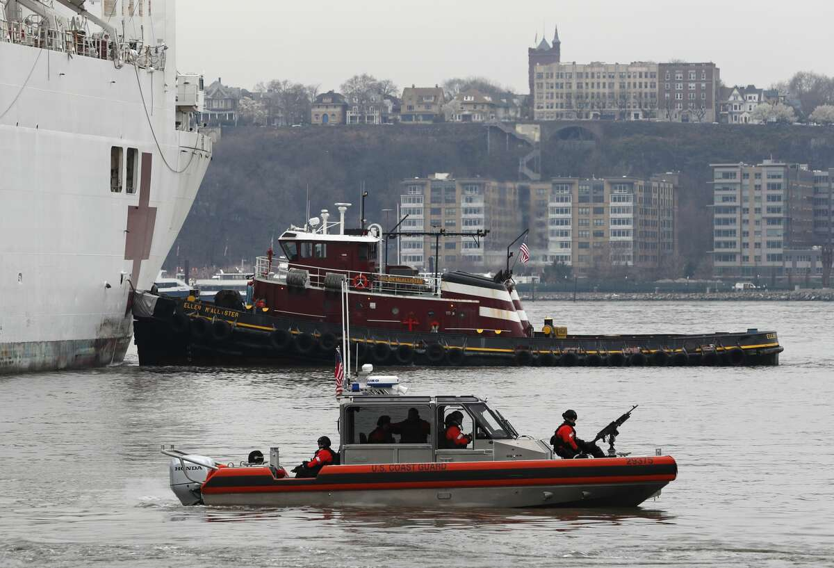 An armed U.S. Coast Guard patrol boat foreground, idles beside the USNS Comfort, a naval hospital ship with a 1,000 bed-capacity, Monday, March 30, 2020, as it pulls into Pier 90 in New York. The ship will be used to treat New Yorkers who don't have coronavirus as land-based hospitals fill up with and treat those who do. (AP Photo/Kathy Willens)
