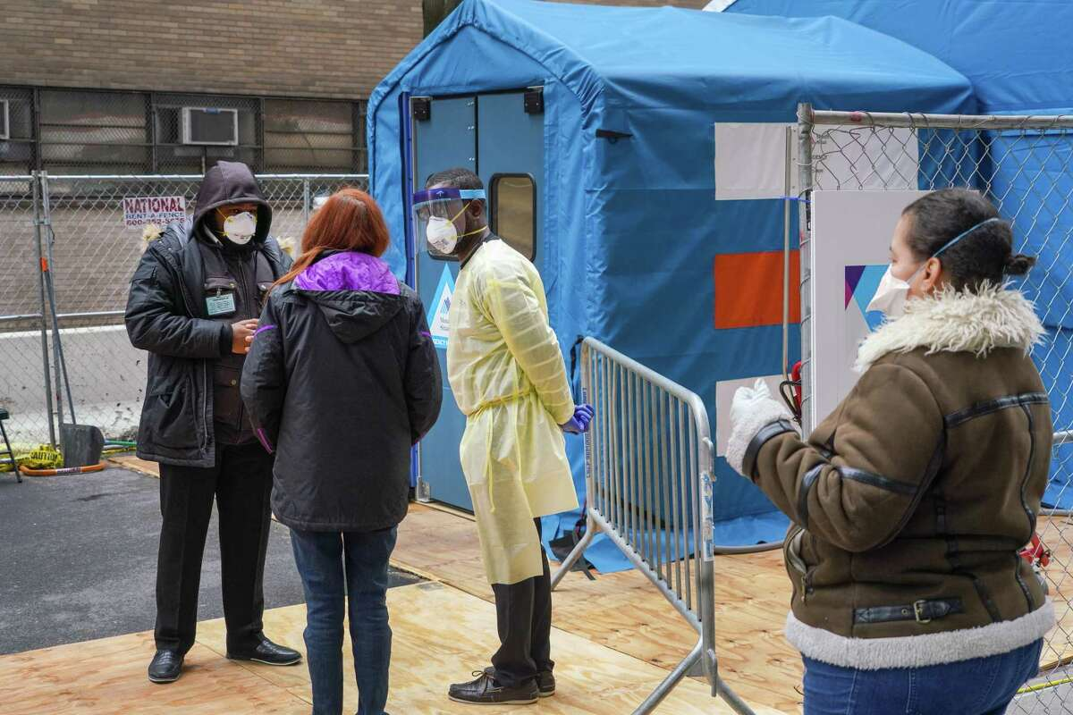 A woman speaks with medical staff before entering the temporary emergency room entrance for testing of the coronavirus at Mount Sinai Hospital West in New York, Friday, April 3, 2020. The coronavirus is taking lives at a devastating pace in New York, Gov. Andrew Cuomo said, with deaths nearly doubling in just three days, from 1,550 on Tuesday to 2,935 on Friday.