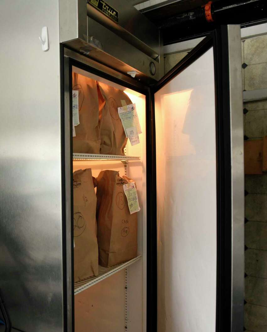 Bags of orders are seen in a freezer in the Snowman-to-go trailer parked behind the main ice cream stand on Friday, April 3, 2020 in Troy, N.Y. Her husband and owner of Snowman, John Murphy, carefully set up everything to deal with social distancing but was forced to close when people ignored the safeguards. He's allowing pre-ordered pickup and trying to figure out how to reopen. (Lori Van Buren/Times Union)