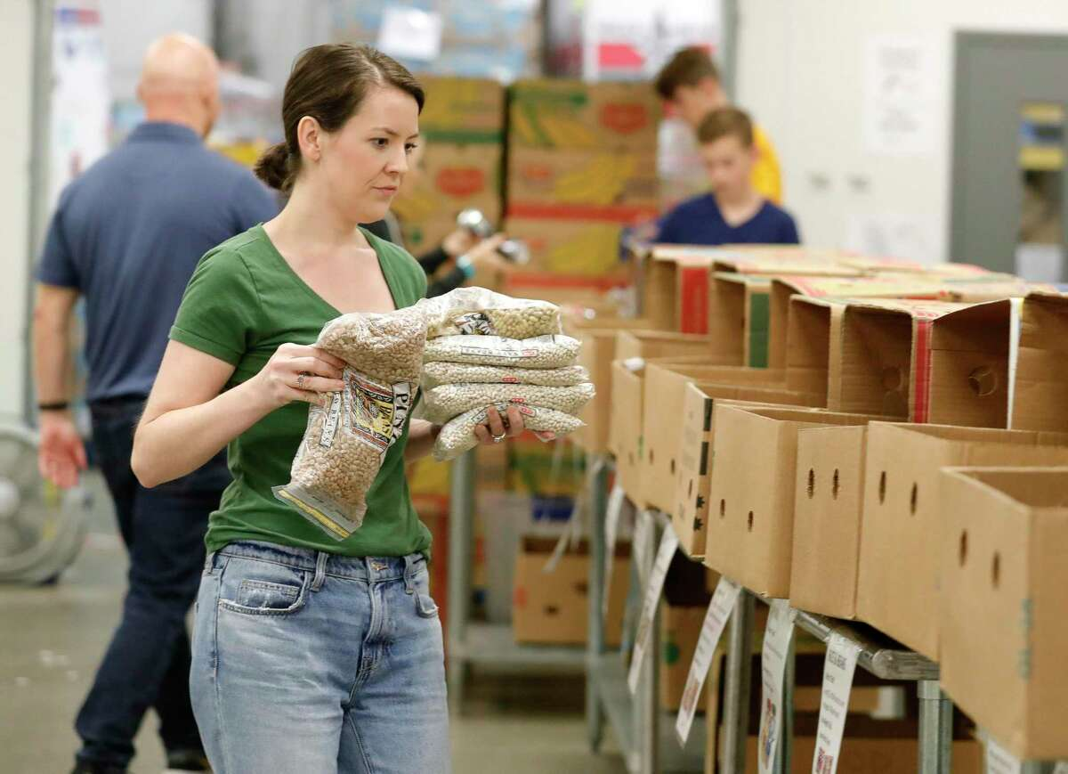 Volunteer Sidney Vance helps sort food at the Montgomery County Food Bank, Friday, March 20, 2020, in Conroe.