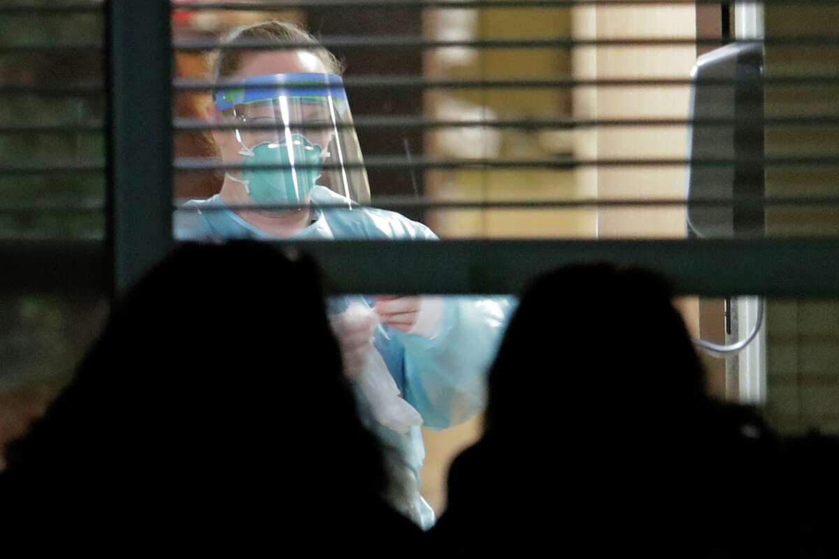 A worker wearing protective gear is seen through a window as she works in the room of Susan Hailey, 76, who has tested positive for the new coronavirus, as Hailey's daughters look in from outside the window, Tuesday, March 10, 2020, at the Life Care Center in Kirkland, Wash., near Seattle. The nursing home is at the center of the outbreak of the new coronavirus in Washington state. (AP Photo/Ted S. Warren)