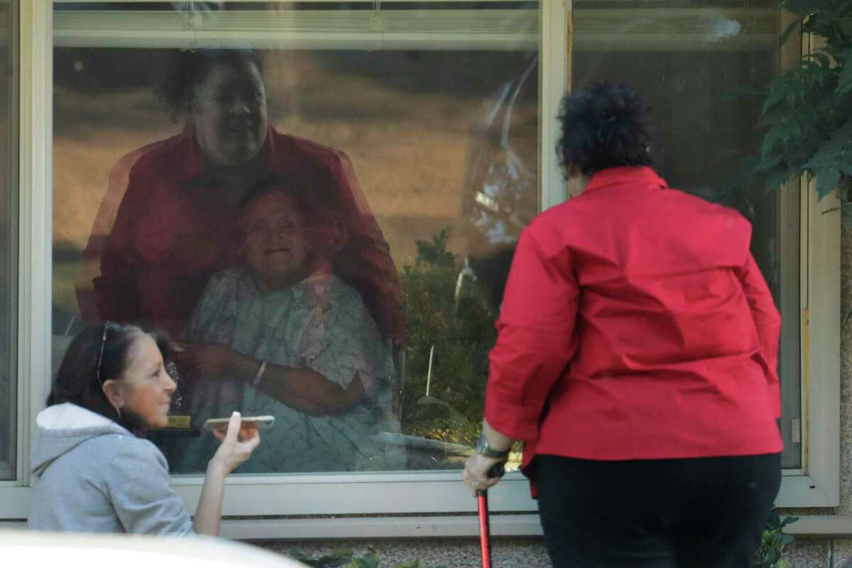 Carmen Gray, left, and her sister, Bridget Parkhill, right, talk on a phone as they visit through a window with their mother, Susan Hailey, 76, center, who has tested positive for the new coronavirus, Friday, March 20, 2020, at the Life Care Center in Kirkland, Wash., near Seattle. In-person visits are not allowed at the nursing home, which has been at the center of the outbreak of the new coronavirus in Washington state. (AP Photo/Ted S. Warren)