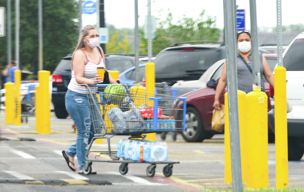Shoppers wear face masks as part of a new city mandate to help reduce the spread of coronavirus COVID-19, Thursday, Apr. 2, 2020, at Wal-Mart.