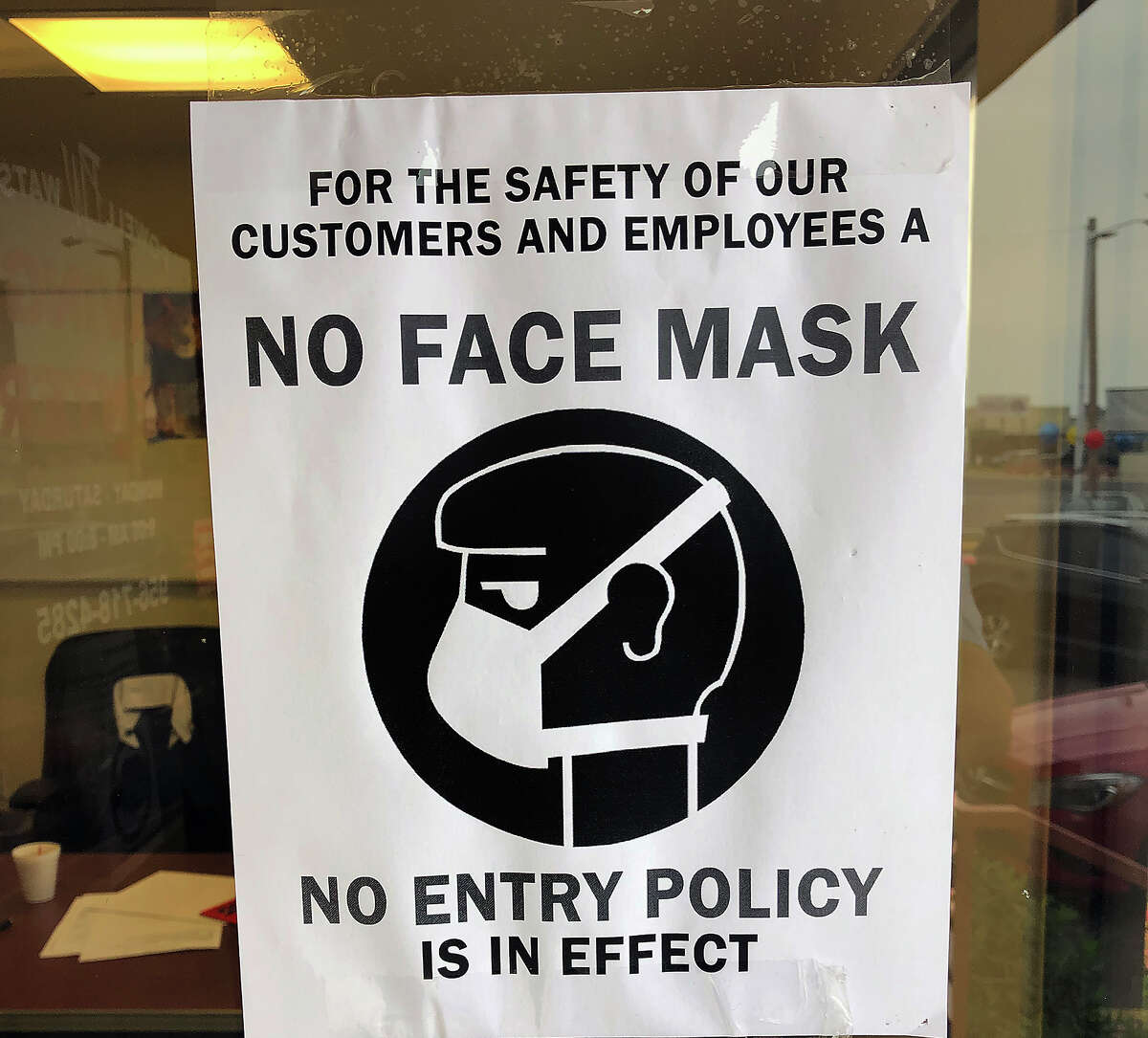 """In this file photo, Powell Watson Savings Center is shown with a sign enforcing a """"No Face Mask, No Entry Policy"""" for the safety of their employees and customers."""