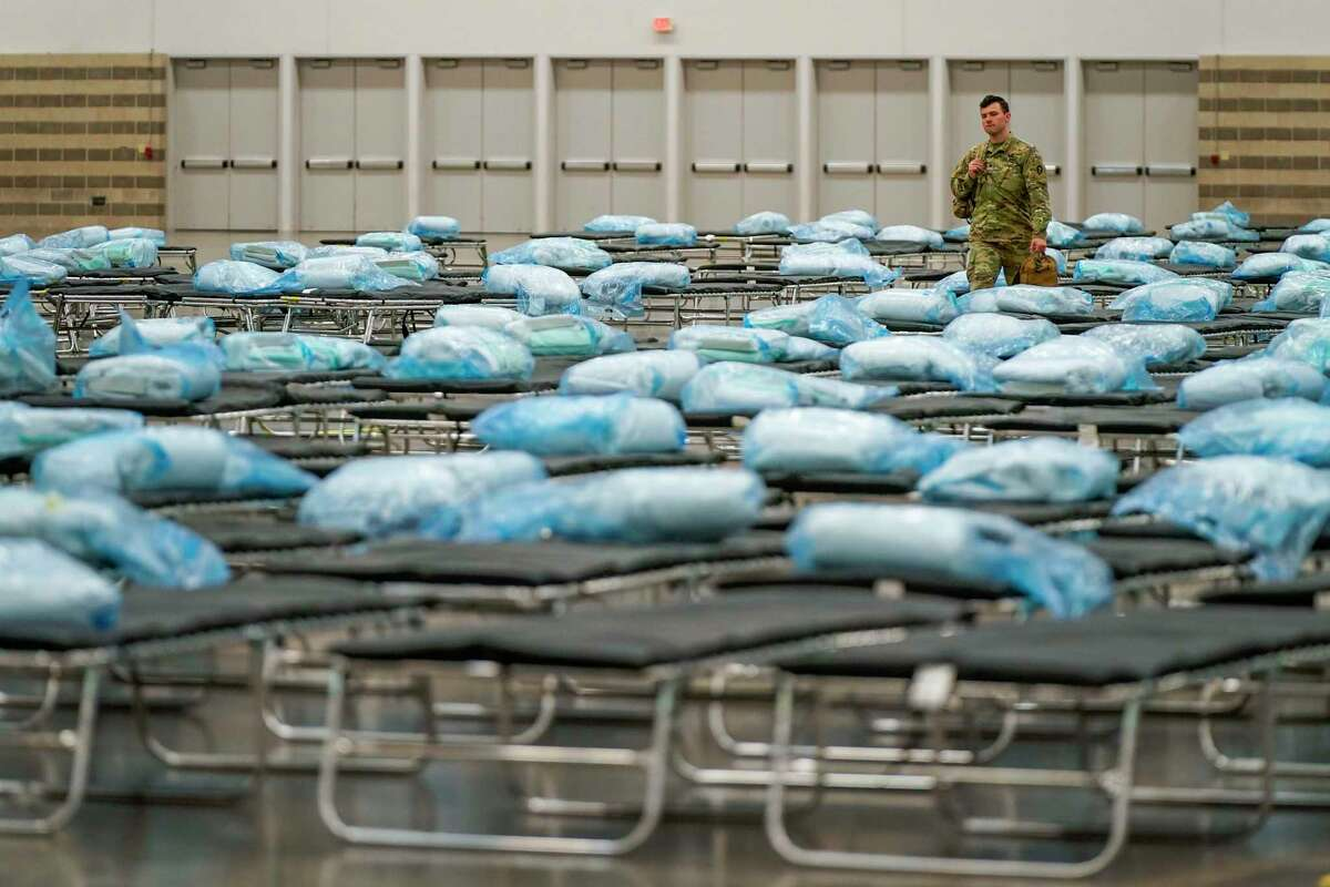 Members of the Texas Army National Guard set up a field hospital in response to the new coronavirus crisis at the Kay Bailey Hutchison Convention Center on Tuesday, March 31, 2020, in Dallas. (Smiley N. Pool/The Dallas Morning News via AP, Pool)