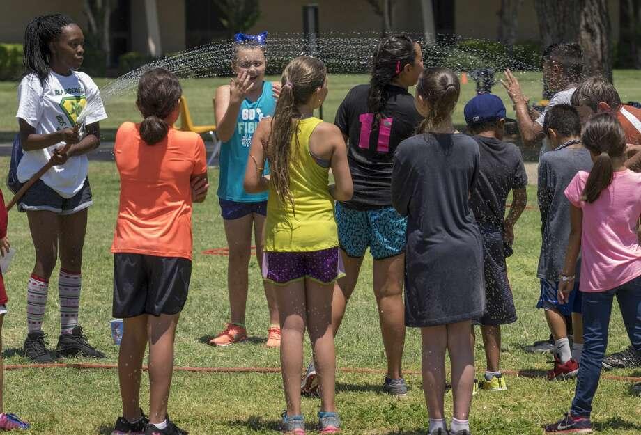 Mylyra Ball, Wild & Crazy Kids teacher, sprays down her campers with a hose to stay cool 6/22/17 during activities at Midland College Kids College. Tim Fischer/Reporter-Telegram Photo: Tim Fischer/Midland Reporter-Telegram