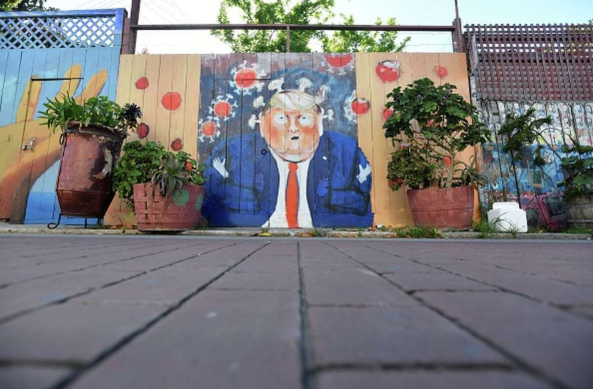 A mural painted on a fence depicts US President Donald Trump as the Coronavirus in San Francisco, California on April, 01, 2020. - All 40 million residents of California were Thursday ordered to stay at home indefinitely in a bid to battle the coronavirus pandemic in the nation's most populous state.