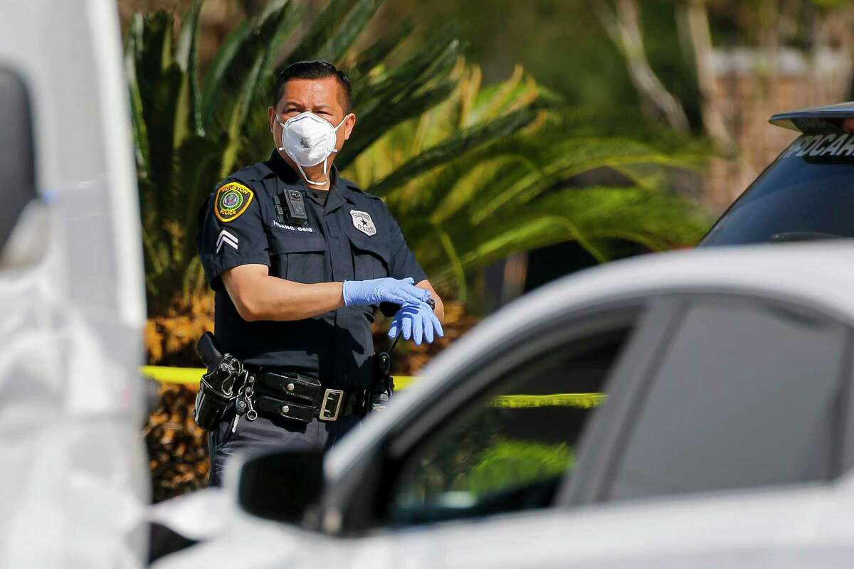 A Houston Police Department officer puts on his gloves to go with a mask he is wearing as he secures a homicide scene, Friday, March 27, 2020, at a strip mall center in west Houston.