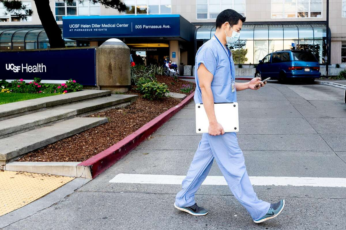 Dr. Peter Chin-Hong checks his phone while walking outside UCSF Medical Center on Friday, April 3, 2020, in San Francisco. Dr. Chin-Hong and fellow UCSF physicians are using Twitter to help educate the public about the frightening and evolving coronavirus outbreak.