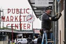 A carpenter, who declined to be identified, covers a closed store with plywood panels in view of the Pike Place Market in downtown Seattle, Thursday, April 2, 2020. The number of people seeking unemployment benefits in Washington set a new record last week, with tens of thousands more people in the state filing new claims as non-essential businesses remain closed due to the ongoing coronavirus pandemic. (AP Photo/Elaine Thompson)