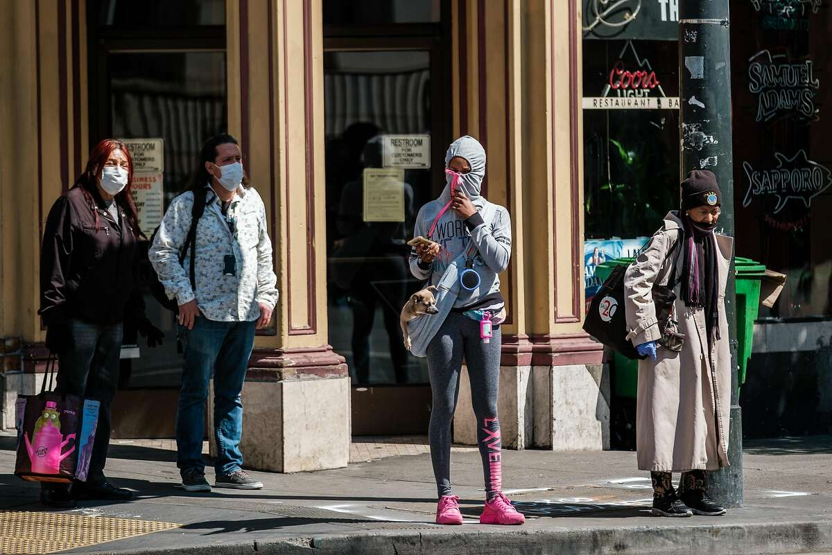 A woman is seen using her hood as a mask as she walks down the street in San Francisco, Calif. on Friday April 3, 2020.