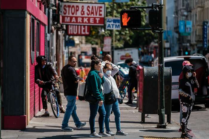A woman is seen wearing a mask as she waits at a crosswalk in San Francisco, Calif. on Friday April 3, 2020.