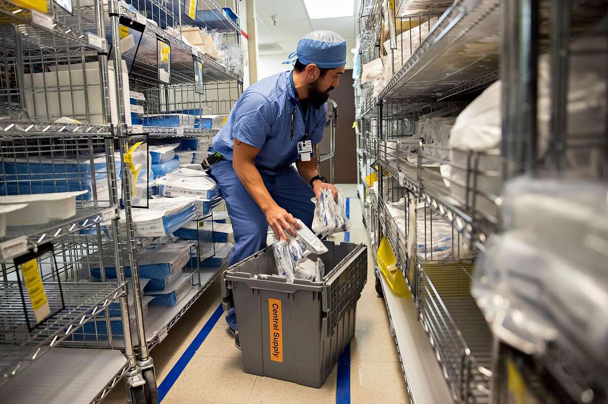 A member of the central supply staff restocks tubings inside a stockroom at Seton Medical Center in Daly City, Calif.