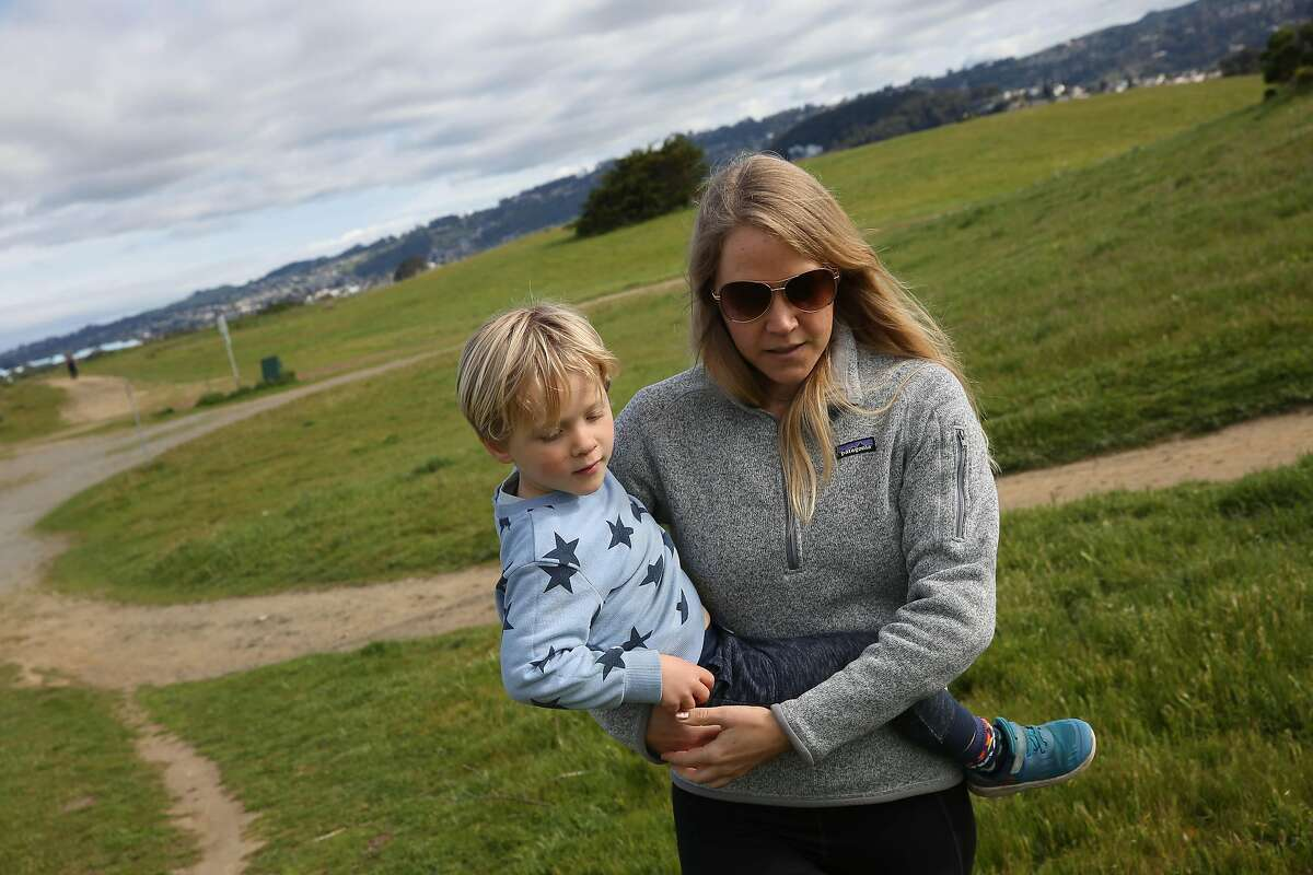 Bethany Hendrickson O'Connell (right), carries her son Charlie O'Connell (left), 4, up a hill as they hike on a trail at C�sar E. Ch�vez Park at the Berkeley Marina on Monday, March 30, 2020 in Berkeley, Calif.