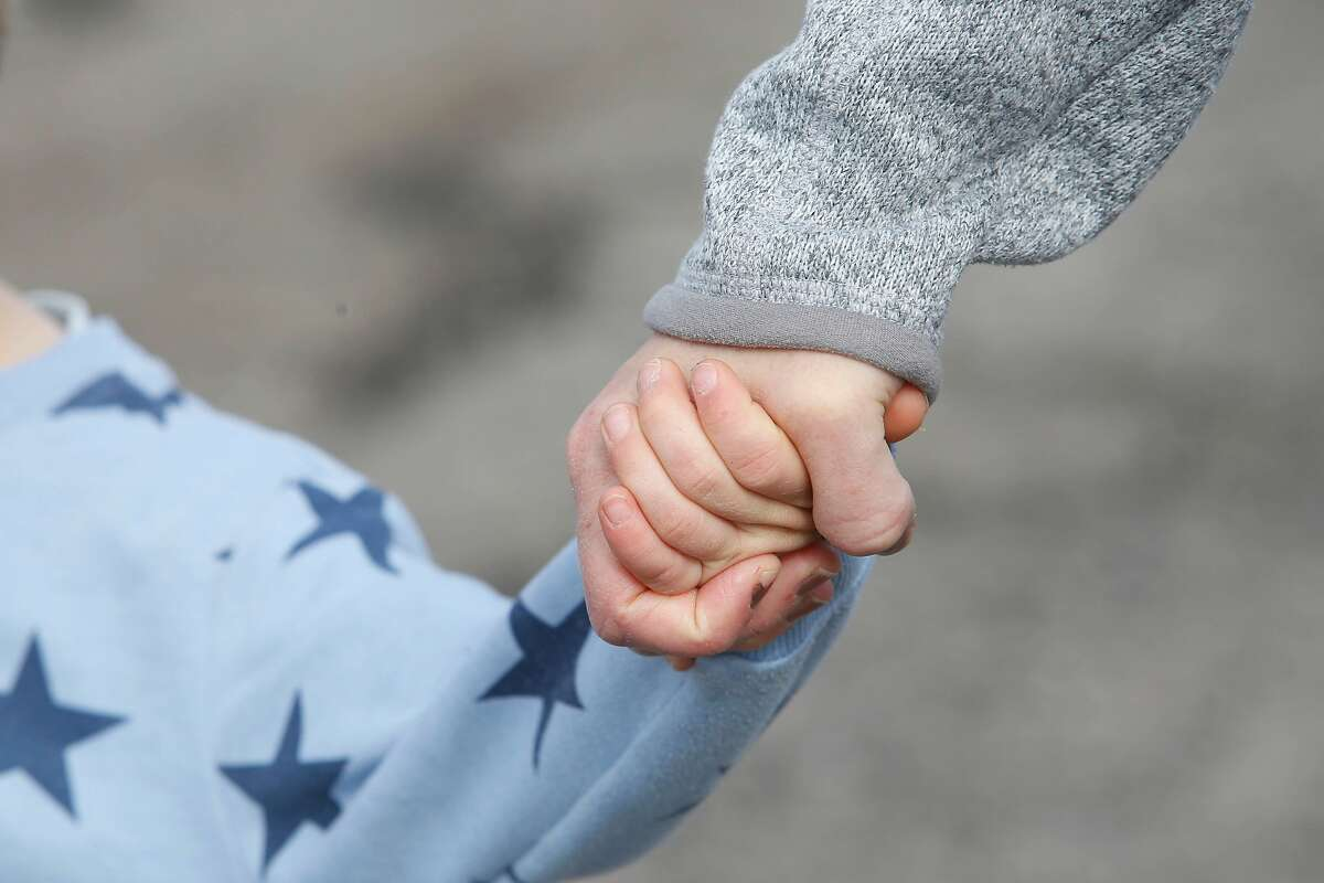 Charlie O'Connell (l to r), 4, and his mother, Bethany Hendrickson O'Connell, hold hands as they hike on a trail together at C�sar E. Ch�vez Park at the Berkeley Marina on Monday, March 30, 2020 in Berkeley, Calif.