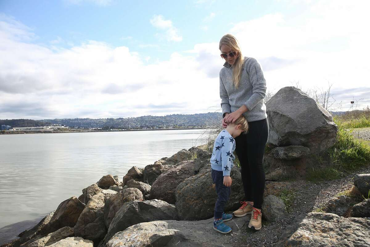 Bethany Hendrickson O'Connell (right) comforts her son Charlie O'Connell (left), 4, as she explains to him that he can't walk down the rocks to the seaweed while enjoying an outing together at C�sar E. Ch�vez Park at the Berkeley Marina on Monday, March 30, 2020 in Berkeley, Calif.