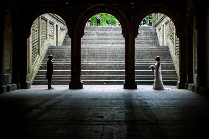 FILE - In this Tuesday, May 23, 2017 file photo, a bride and groom pose for wedding pictures at the Bethesda Terrace in New York's Central Park. Now that most Americans have been ordered to stay at home and avoid nonessential travel to slow the spread of the COVID-19 coronavirus in 2020, many couples a€?
