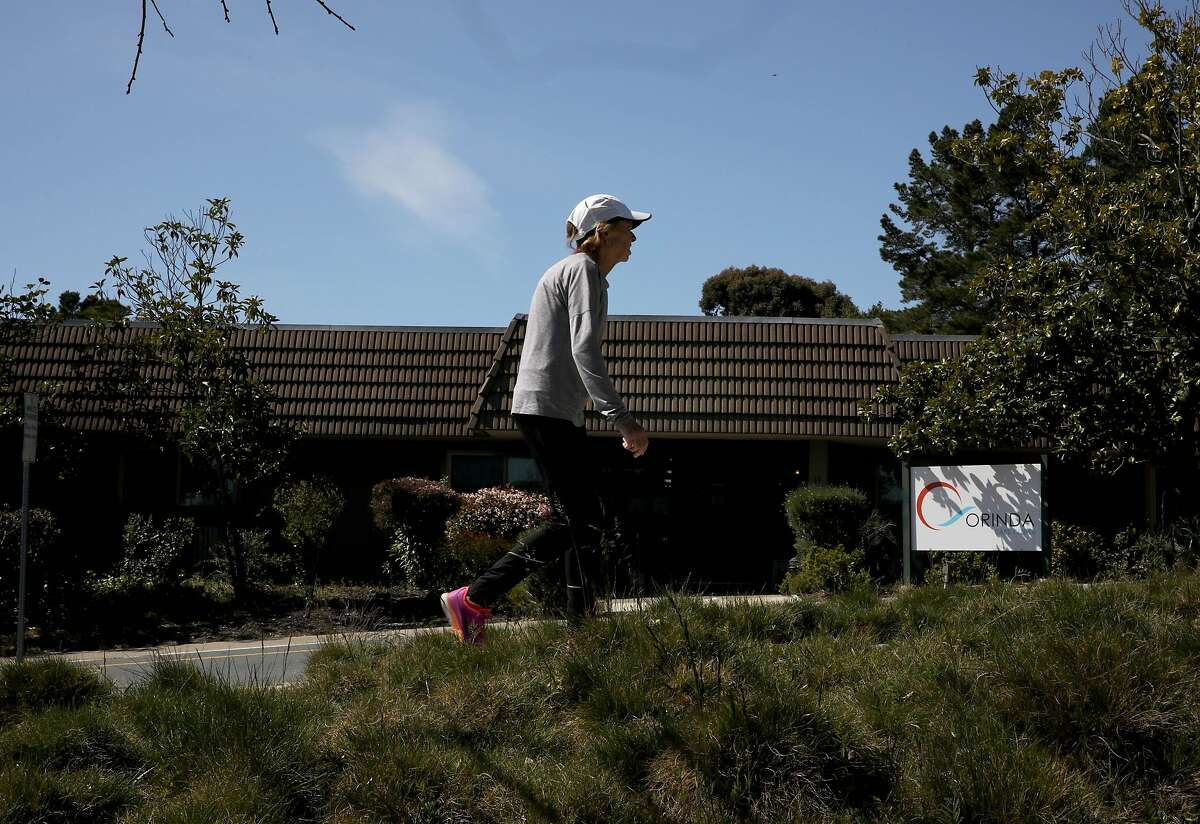 """A pedestrian passes the Orinda Care Center, located at 11 Altarinda Rd., on Friday, April 3, 2020, in Orinda, Calif. Contra Costa officials release more info on outbreak at nursing facility, launch investigations into two more facilities: At least 27 people who live or work at a 45-resident nursing facility in Orinda have tested positive for the coronavirus, health officials said Friday as they launched investigations and started testing at two other senior care facilities in the county. Officials started investigating the Orinda Care Center this week when two staffers sought sought medical care, according to the county Health Services. The two staffers and two patients tested positive on Wednesday. County health officials tested all patients and staff Thursday, they said, and confirmed 24 patients and three staffers had the virus. They are still awaiting some test results. Two of the residents are being treated at hospitals. As of Friday morning, no staffers or patients had died of the virus. Staffers and residents who do not have serious symptoms are medically isolated but not hospitalized, officials said. """"The situation is very serious, and we are deeply concerned about residents of our senior care facilities in Contra Costa County,"""" said Dr. Chris Farnitano, the county's health officer. """"That is why we need everyone to follow the stay-at-home order, social distancing guidance and other measures in recent health orders ? to protect the people in our community who are vulnerable to severe illness from COVID-19."""""""