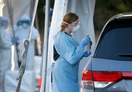 A health care worker speaks with a driver at a drive- through  coronavirus testing site in a parking lot of the old California Pacific Medical Center on California Street in San Francisco on Thursday.