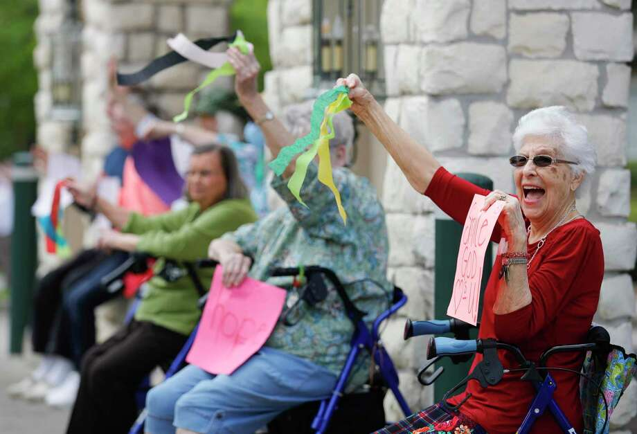 Catherine Moore waves to passing cars as residents of the Carriage Inn Conroe assisted living facility take in a parade from friends, family and other community members, Friday, April 3, 2020, in Conroe. Photo: Jason Fochtman,  Houston Chronicle / Staff Photographer / 2020 © Houston Chronicle