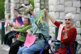 Catherine Moore waves to passing cars as residents of the Carriage Inn Conroe assisted living facility take in a parade from friends, family and other community members, Friday, April 3, 2020, in Conroe.