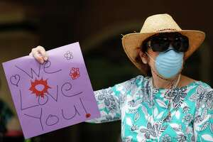Betty Handley holds up a sign while wearing a mask as residents of the Carriage in Conroe assisted living facility take in a parade from friends, family and other community memebers. Montgomery County now has 161 COVID-19 cases, logging a dozen more Monday.