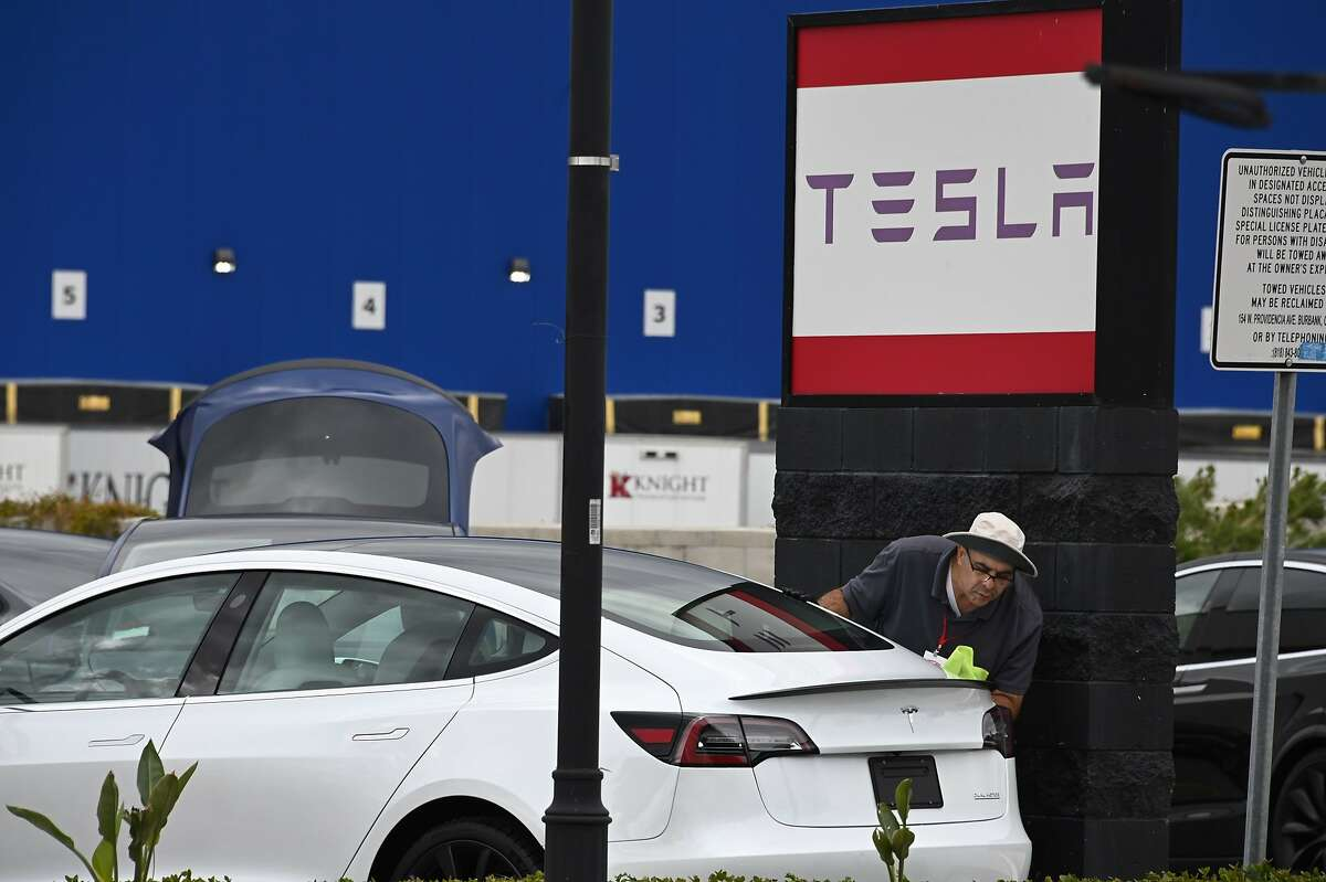 A Tesla employee cleans a car outside a Tesla showroom in Burbank, California, March 24, 2020. - Luxury electric car maker Tesla ended up closing its California plant in Fremont, a concession by its maverick head Elon Musk after a drawn-out standoff with the state authorities over the spread of the virus.