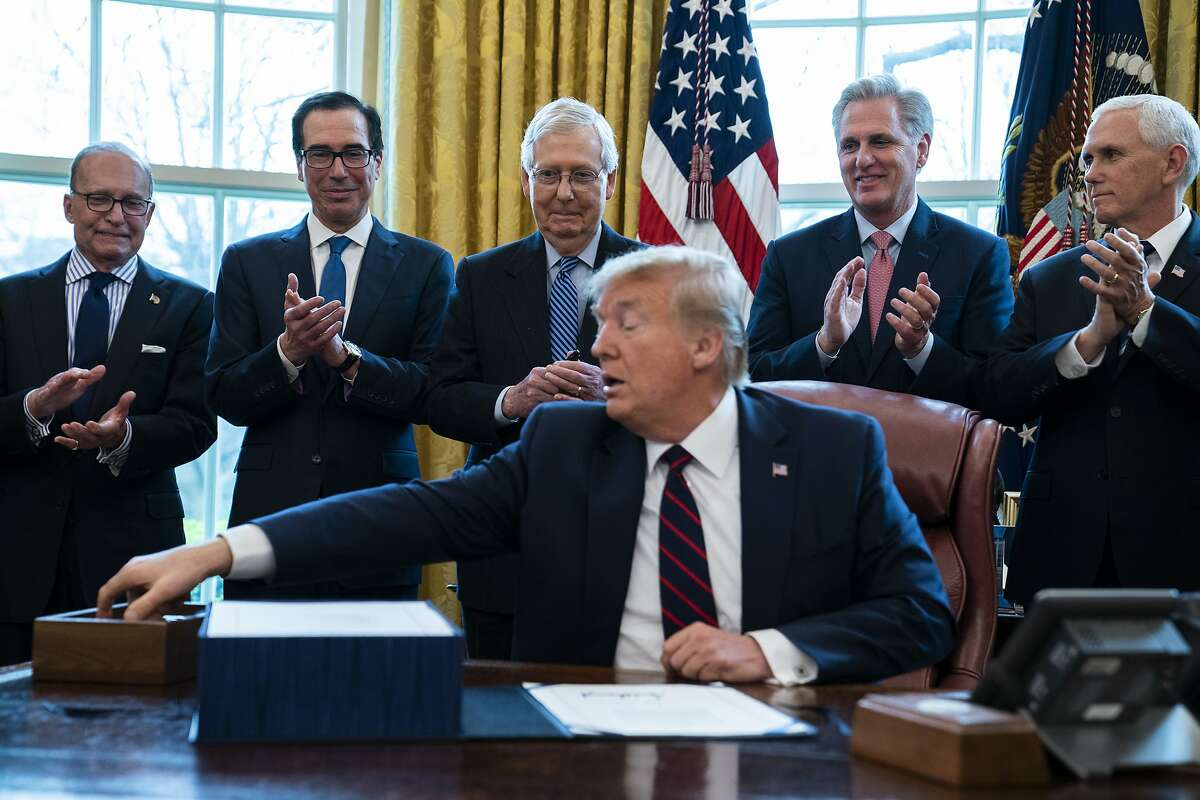President Donald Trump reaches for a pen during a ceremony to sign the coronavirus stimulus relief package in the Oval Office at the White House, Friday, March 27, 2020, in Washington. From left, White House chief economic adviser Larry Kudlow, Treasury Secretary Steven Mnuchin, Senate Majority Leader Mitch McConnell of Ky., Trump, House Minority Leader Kevin McCarty, R-Calif., and Vice President Mike Pence. (AP Photo/Evan Vucci)