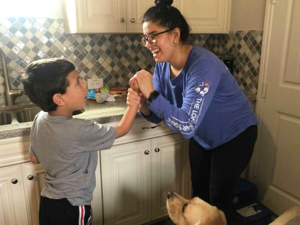 Tommy Dehne works on his lessons with his teacher Tatiana Soto at home. She guides him using hand-over-hand techniques - such as hand-washing or forming a fist for American Sign Language - They also practice imitation of gross motor skills.