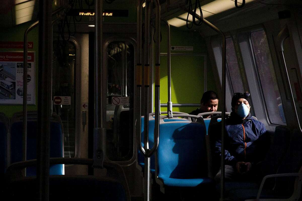 A man rests his eyes while wearing a mask on a Richmond-bound train from 19th Street BART Station in Oakland, Calif. Friday, April 3, 2020. Although BART has seen a drastic decline in ridership, those who still use their services have been seen wearing protective gear and practicing social distancing.