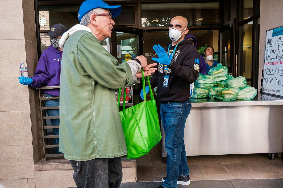 St Anthony's executive director, Jose Ramirez, hands out meals to those in need in San Francisco, Calif. on Thursday April 2, 2020.
