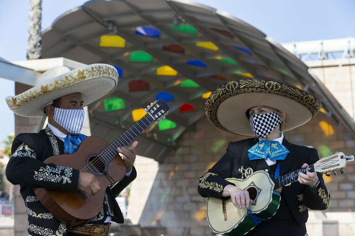 Mariachi players Aurelio Reyes and Sally Hawkridge, who are married, wear handmade face masks as they play at El Mariachi Plaza in the Boyle Heights area of Los Angeles on Wednesday, April 1, 2020. Los Angeles Mayor Eric Garcetti has recommended that the city's 4 million people wear masks when going outside amid the spreading coronavirus. (AP Photo/Damian Dovarganes)