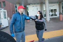 (Left to right) Alex Melzer of Early Bird Tacos elbow bumps with Head nurse Shannon Keeny while delivering food to medical staff at Zuckerberg San Francisco General Hospital in San Francisco, Calif. on April 2, 2020. Early Bird Tacos is donating over 200 breakfast tacos and 120 cups of Equator coffee to feed workers in the Emergency and ICU departments at SF General Hospital.