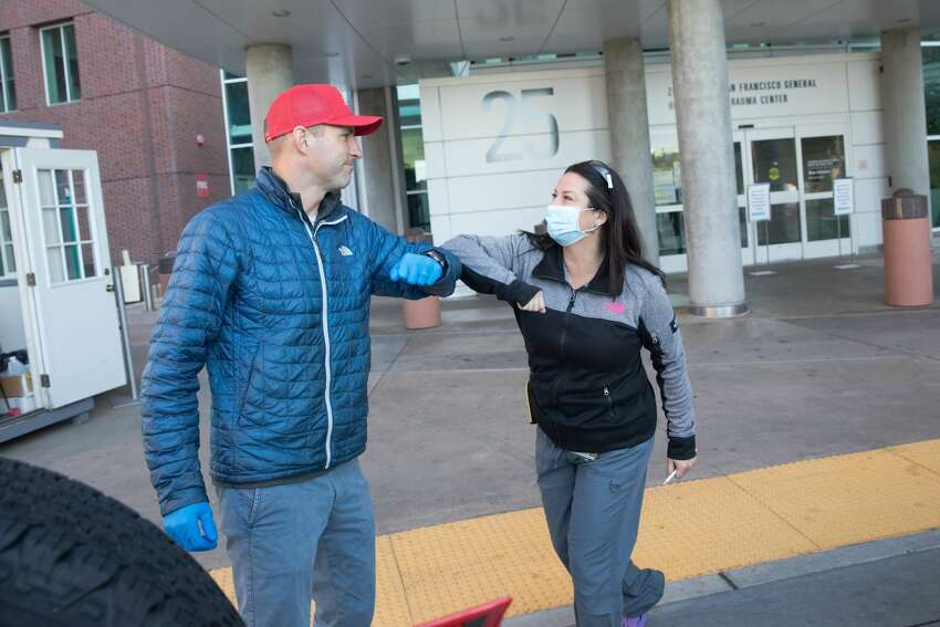 (Left to right) Alex Melzer of Early Bird Tacos elbow bumps with head nurse Shannon Keeny while delivering food to medical staff at Zuckerberg San Francisco General Hospital on April 2, 2020. Early Bird Tacos is donating over 200 breakfast tacos and 120 cups of Equator coffee to feed workers in the emergency and ICU departments.