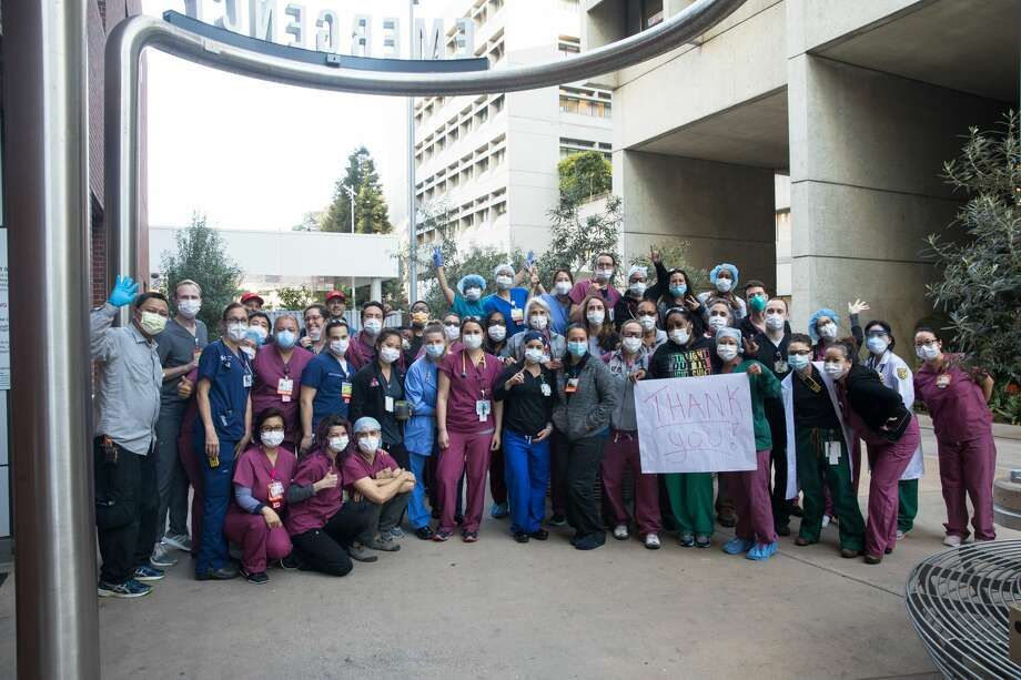 Zuckerberg San Francisco General Hospital nurses gather to take a group photo with Early Bird Tacos staff outside the emergency room in San Francisco on April 2, 2020. Early Bird Tacos is donating over 200 breakfast tacos and 120 cups of Equator coffee to feed workers in the emergency and ICU departments. Photo: Douglas Zimmerman/SFGate / SFGate