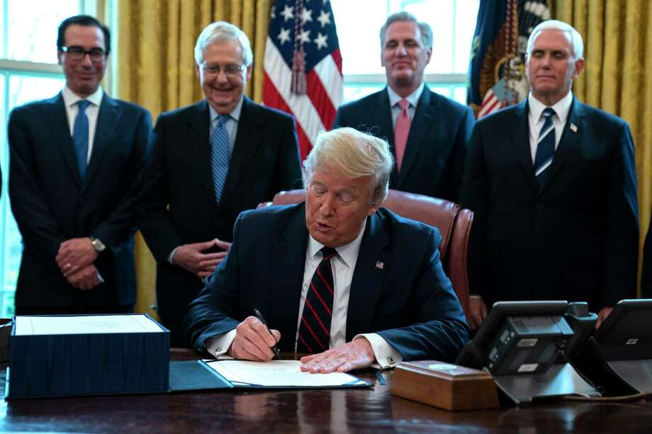 FILE - In this March 27, 2020 file photo, President Donald Trump signs the coronavirus stimulus relief package in the Oval Office at the White House in Washington, as Treasury Secretary Steven Mnuchin, Senate Majority Leader Mitch McConnell, R-Ky., House Minority Leader Kevin McCarty, R-Calif., and Vice President Mike Pence watch. Payments from a federal coronavirus relief package could take several weeks to arrive. While you wait, prep your finances and make a plan for using any money you receive.  (AP Photo/Evan Vucci, File) Photo: Evan Vucci / Copyright 2020 The Associated Press. All rights reserved